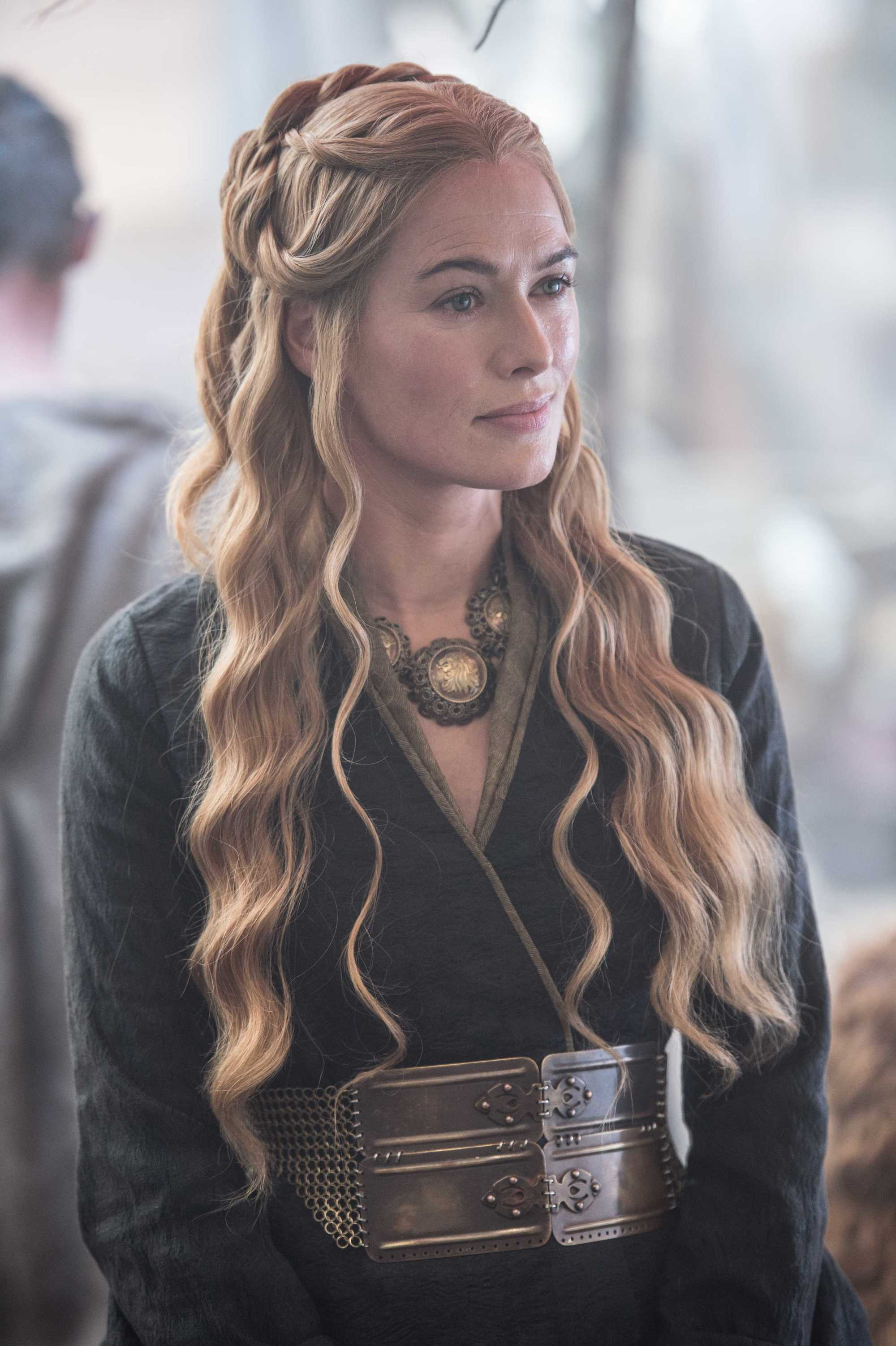 Easy renaissance hairstyles: Game of Thrones' Cersei Lannister with long honey blonde hair styled into half-up, half-down waves, wearing all black on set