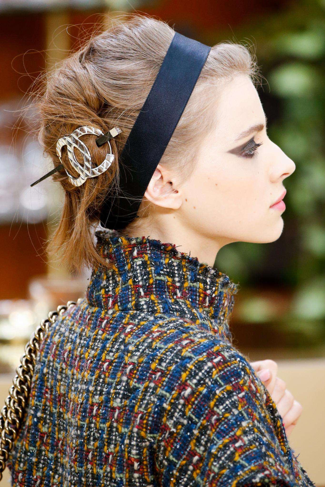close up shot of model on the chanel runway with vintage updo hairstyle with hair accessory, wearing chanel clothing