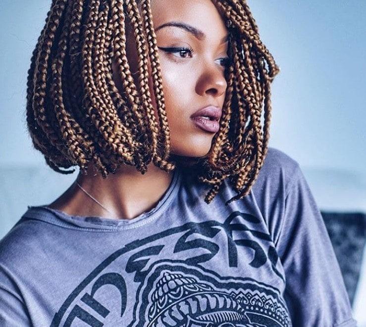 Box braids bob: Woman with caramel brown short bob box braids hairstyle, wearing a grey top