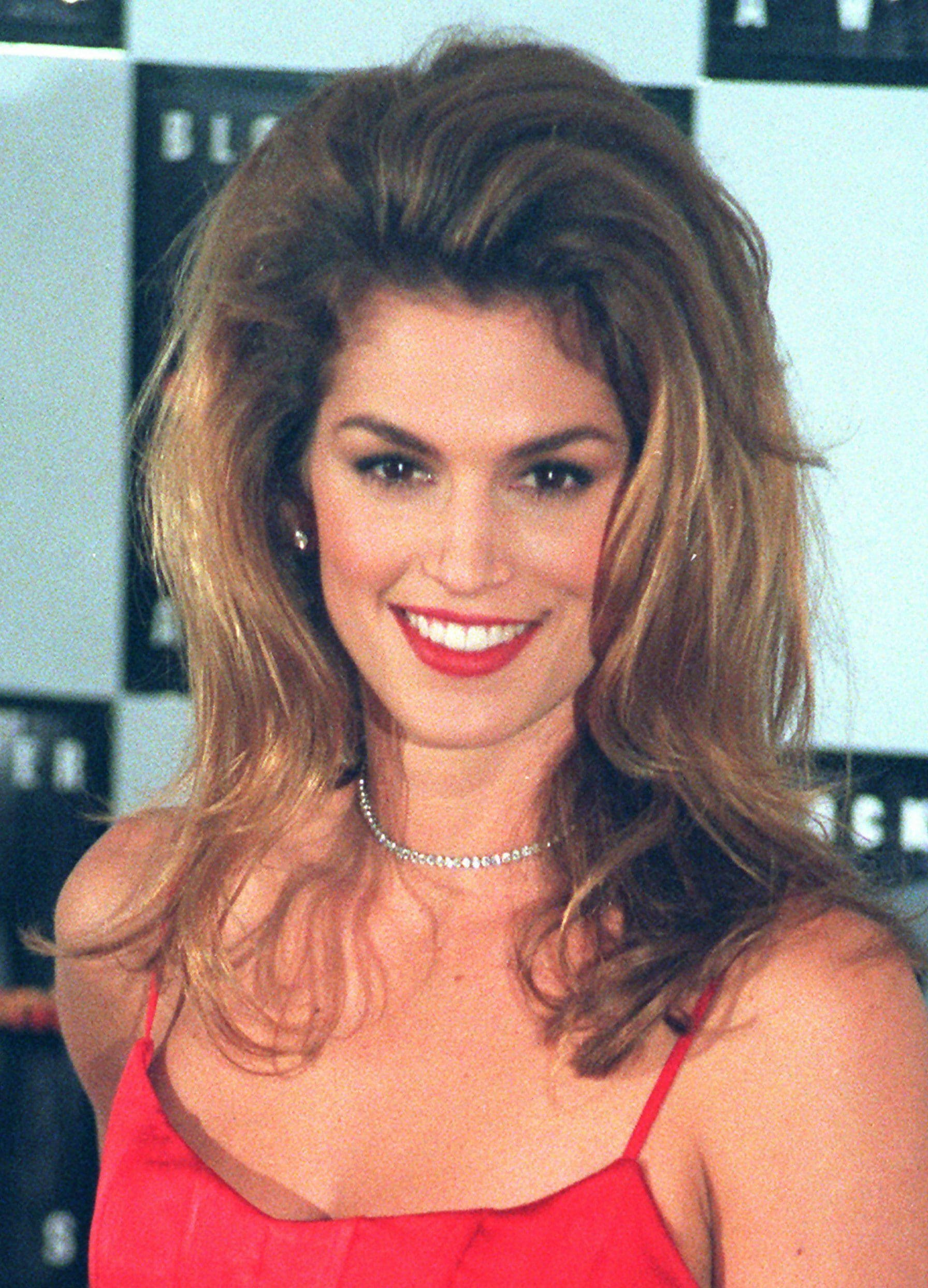 90s hairstyles: Cindy Crawfod big '90s blowout on brown highlighted hair. Cindy is wearing a red camisole dress and red lipstick
