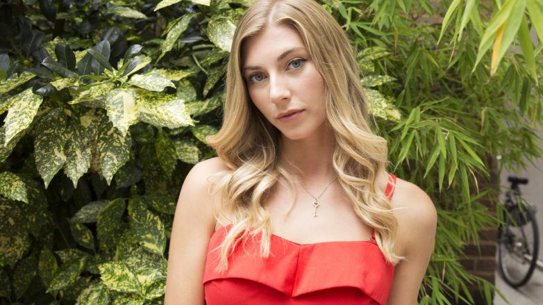 How to curl your hair with a curling wand: Final look of blonde model wearing a red dress
