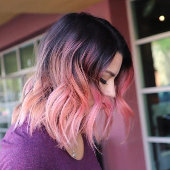 Unicorn hair: Side view of a woman with shoulder length dark brown to pink ombre hair