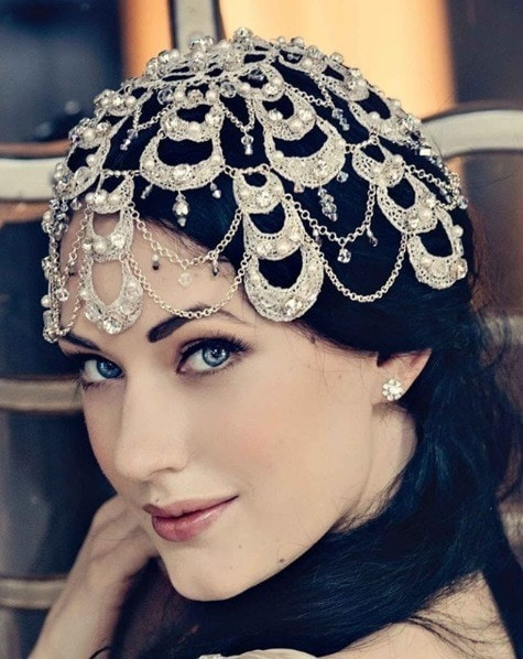 Close-up of a woman with dark brown hair in a low side ponytail, wearing a pearl embellished 1920s head piece