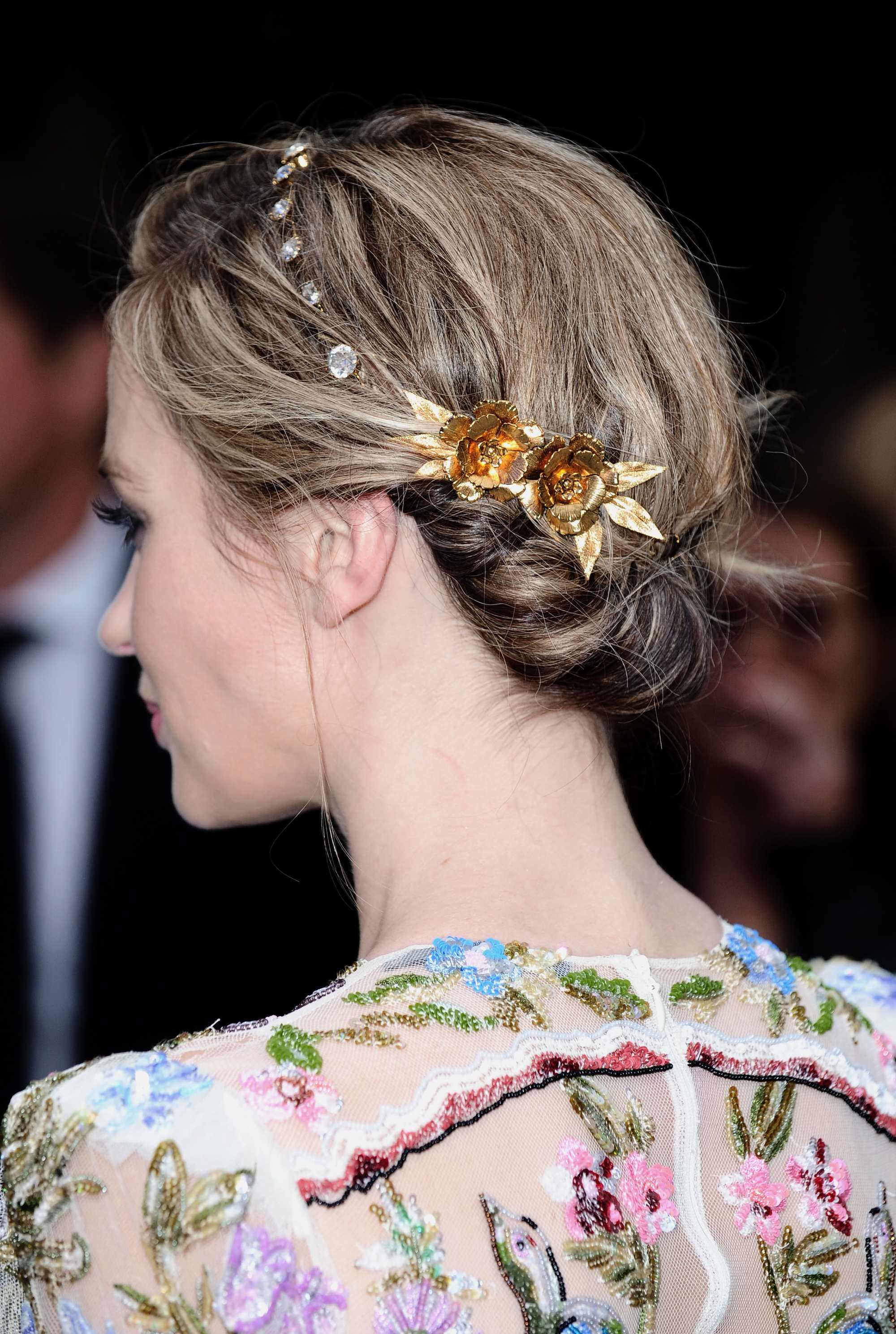 grecian hairstyles: backstage of emily blunt with tuck hairstyle with golden jewellery on it