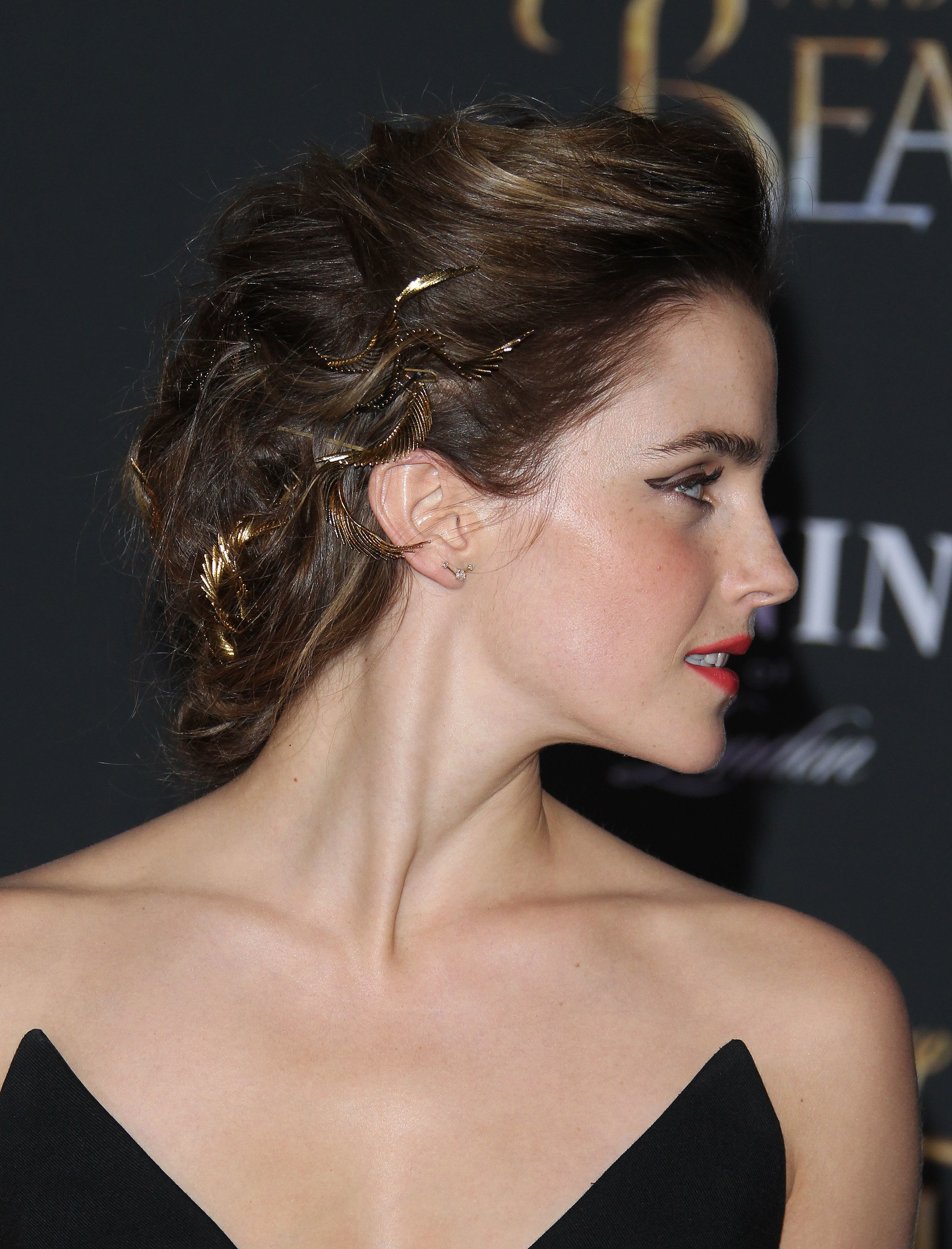 side shot of emma watson with greek inspired messy updo with leaf detailing in it