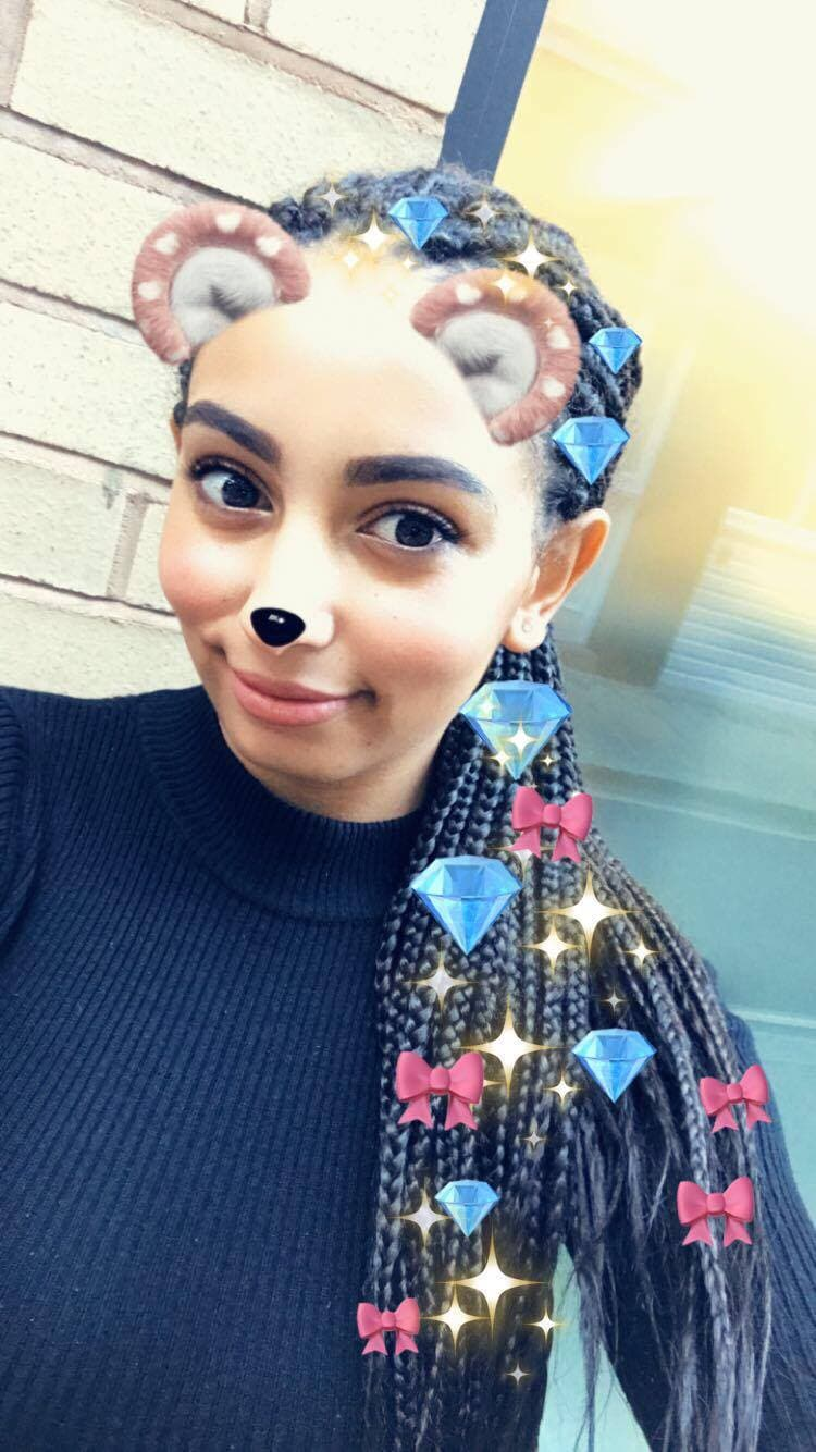 close up shot of Amra (ATH Editor) with side box braids ponytail with emoji all over it
