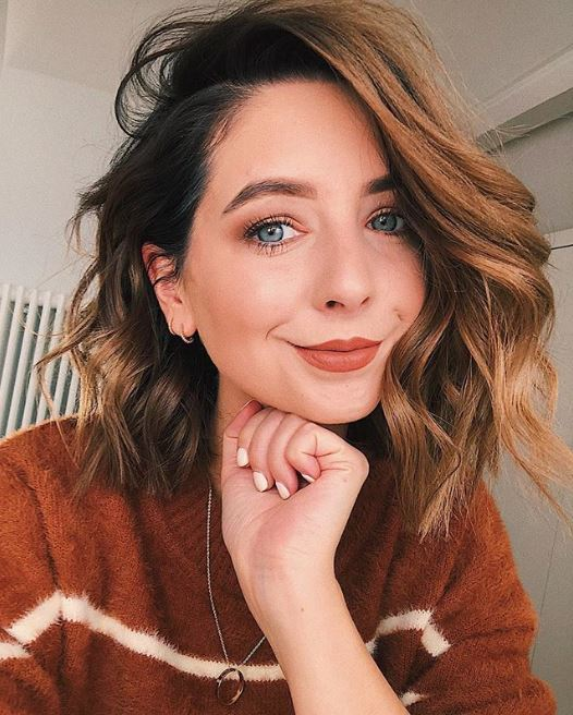 Fall hair colours: Zoe Sugg Zoella with a cinnamon wavy bob wearing a brown jumper resting her chin on her hand.
