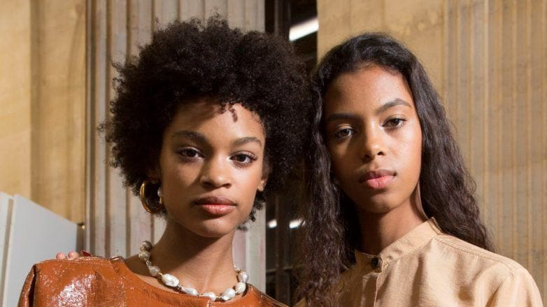 Detangling natural hair: Close up shot of two woman with natural hairstyles backstage