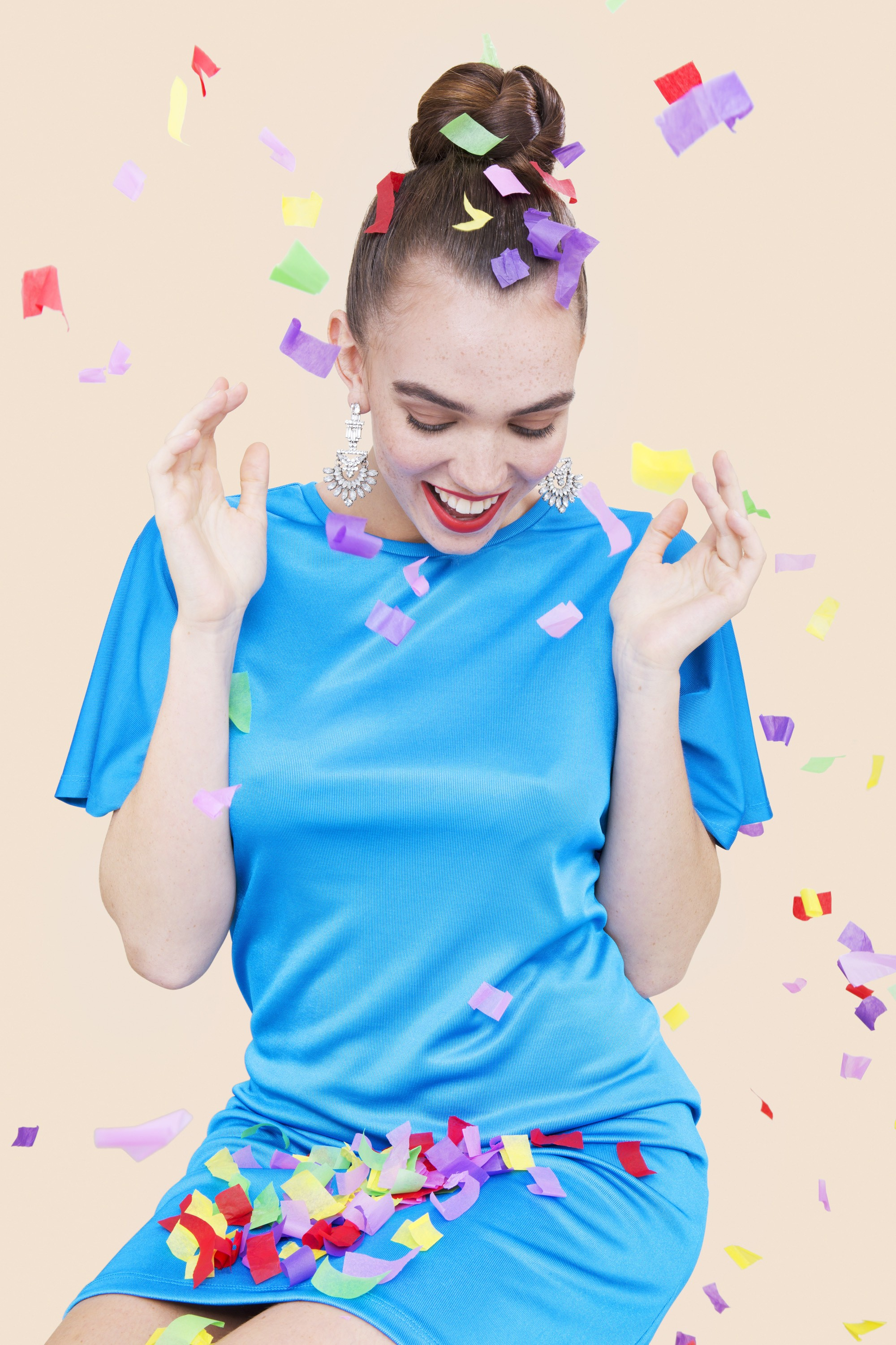 shot of model in a studio with braided bun hairstyle, wearing blue dress, with party poppers everywhere