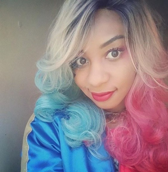 Selfie of a woman with blonde curly hair with blue and pink ombre tips, wearing a silky blue bomber jacket