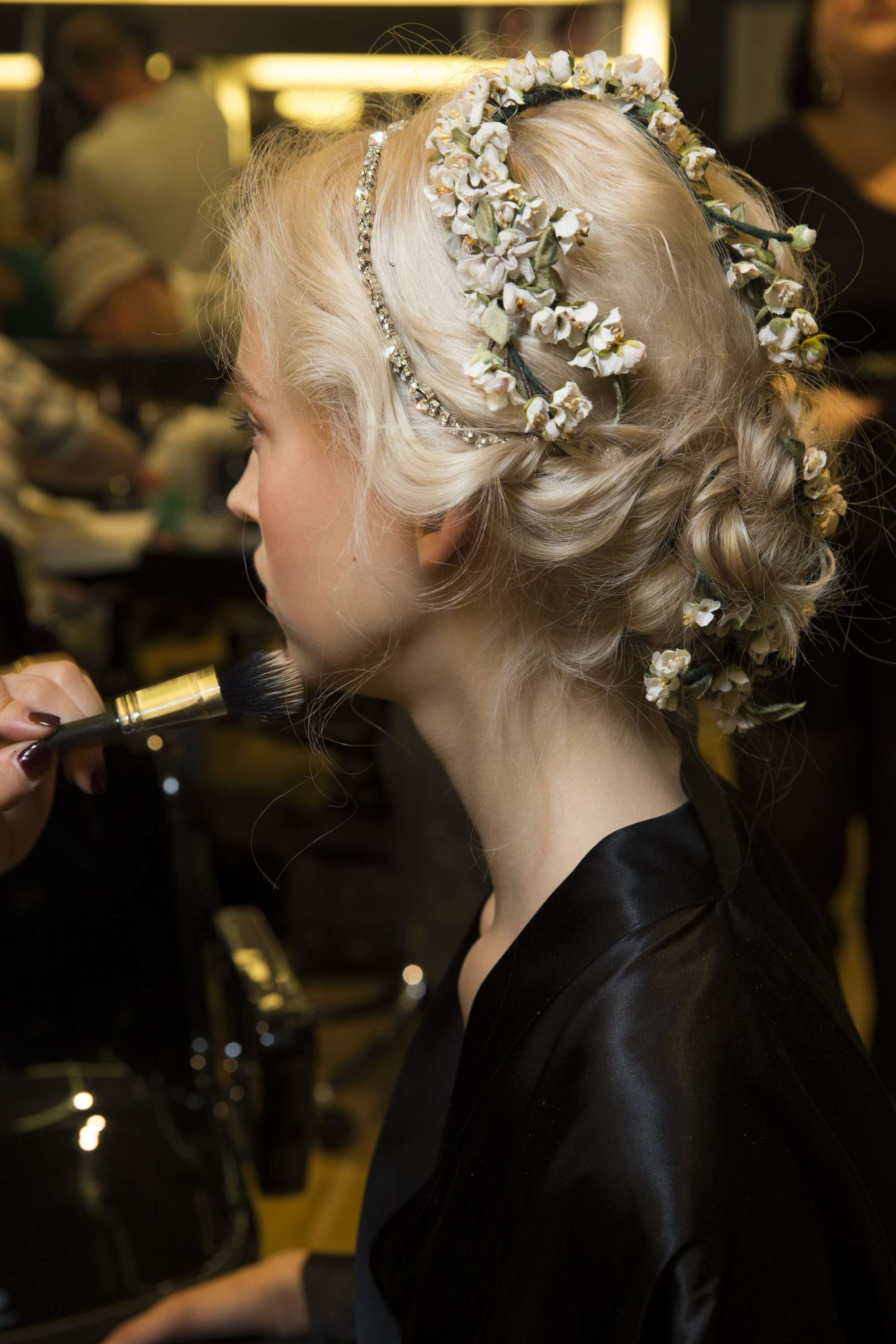 greek hairstyles: shot of model with flowers in an updo backstage