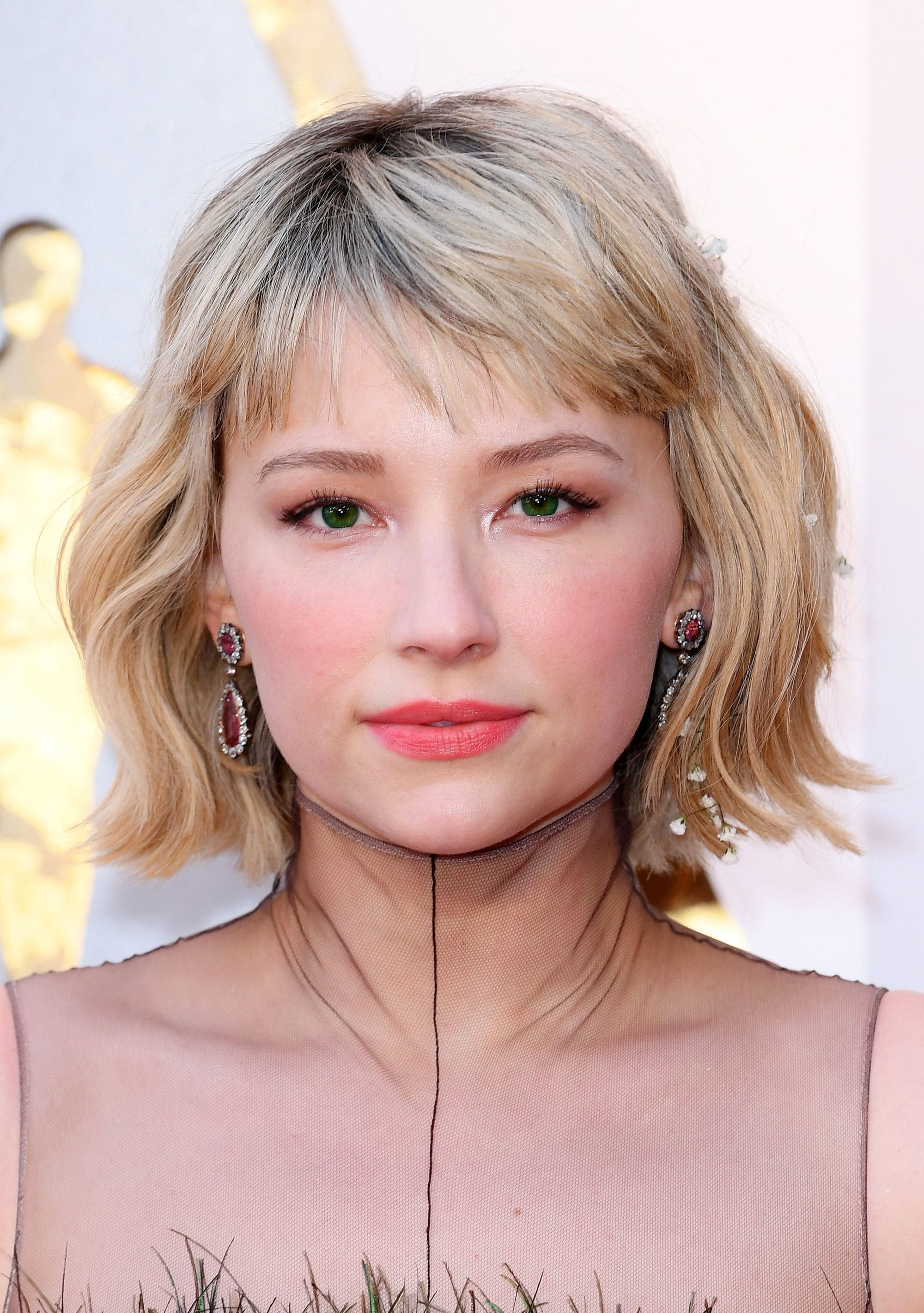 90s hairstyles: Haley Bennett blonde wavy bob with short side fringe on red carpet with high neck sheer dress