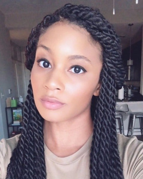 Close-up selfie of a woman with dark brown shiny long box twists in a half-up half-down style.