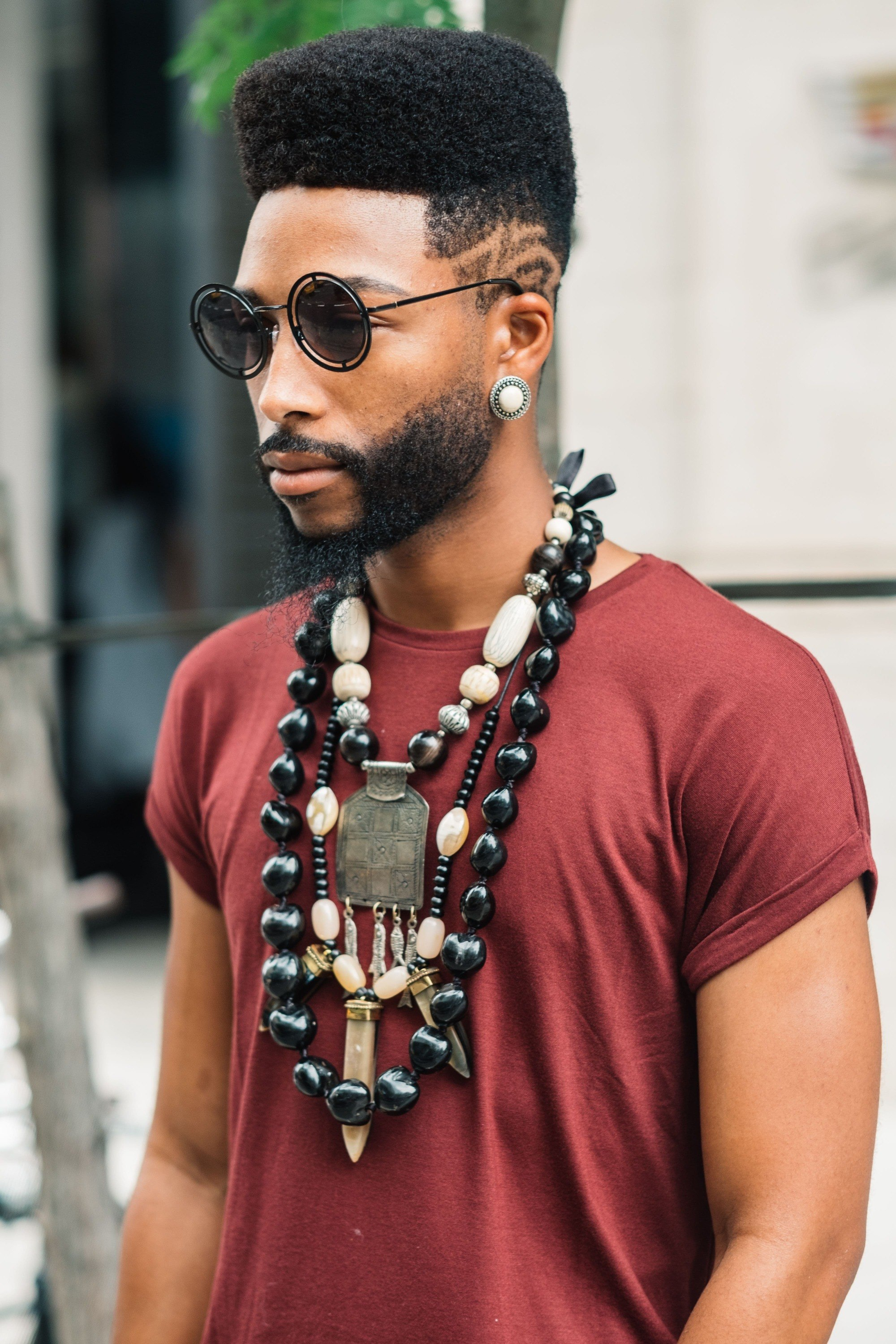 Vintage hairstyles for men: Street style shot of a man with an afro high top with a low fade hairstyle, wearing a red top and necklaces