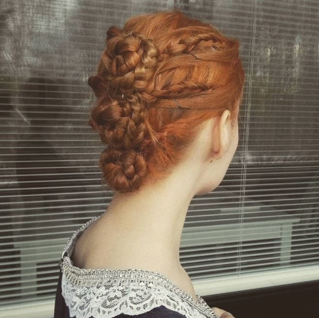Renaissance updo: Woman with ginger hair in a triple braided bun renaissance hairstyle