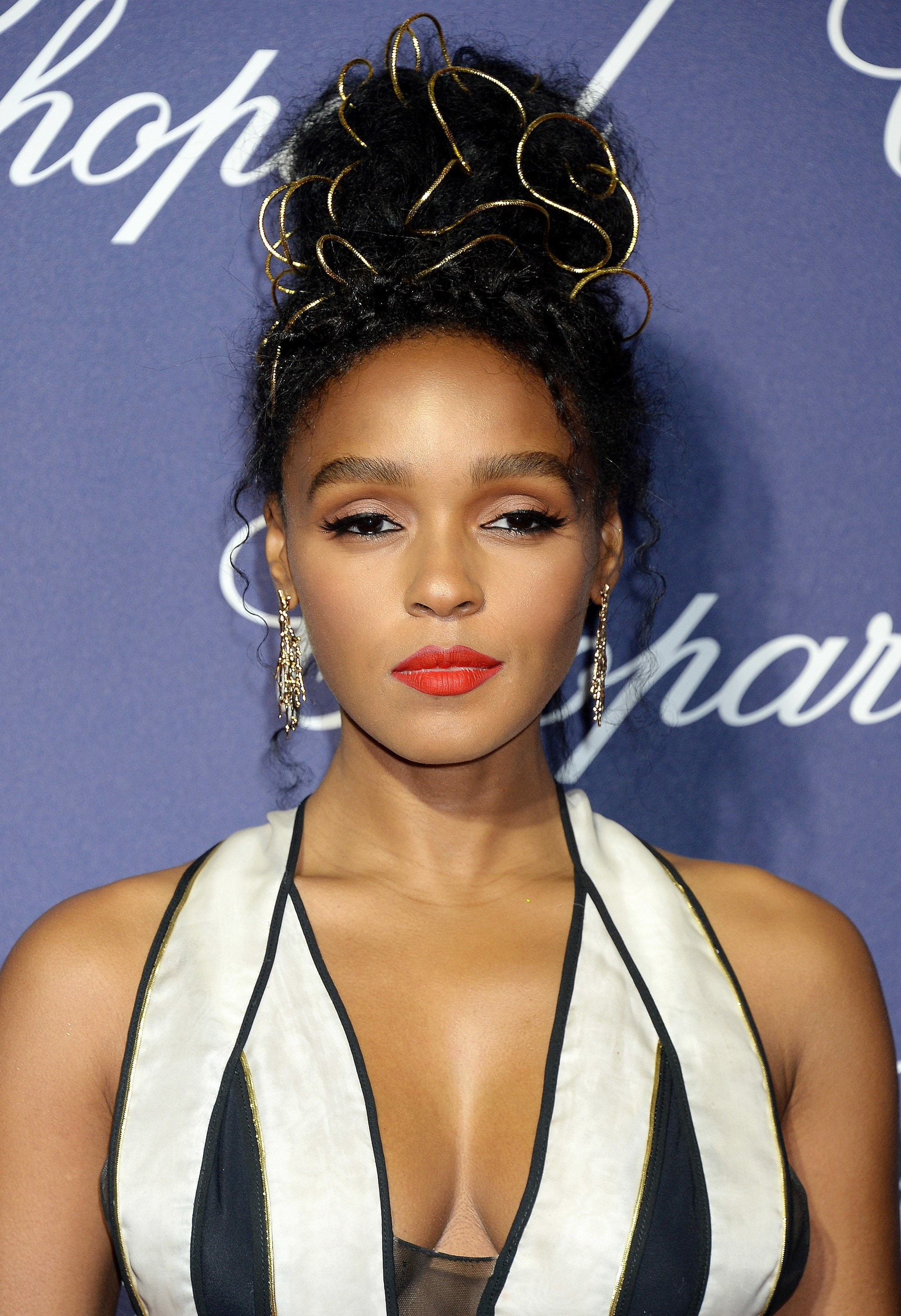greek hairstyles: close up shot of janelle monae with golden puff hairstyle at palm springs event