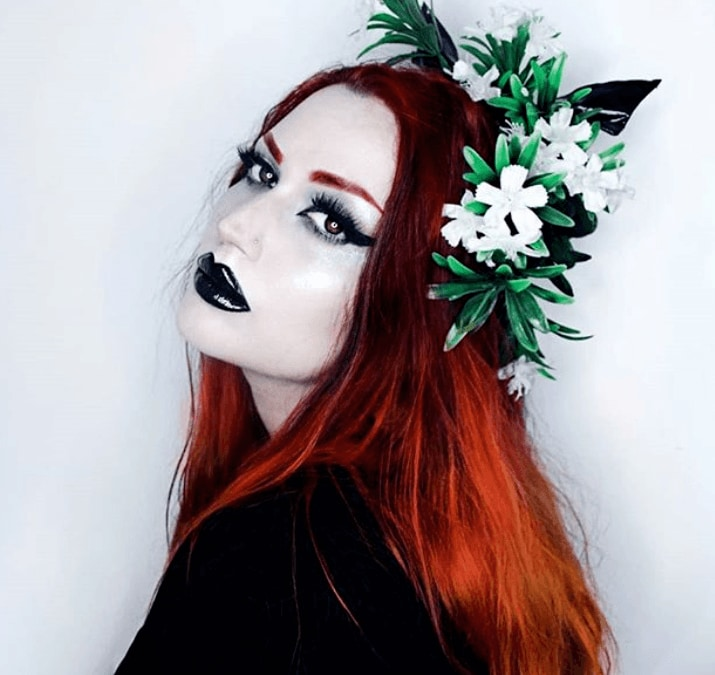 Goth hairstyles: Gothic woman with copper red hair wearing a flower crown with a black outfit