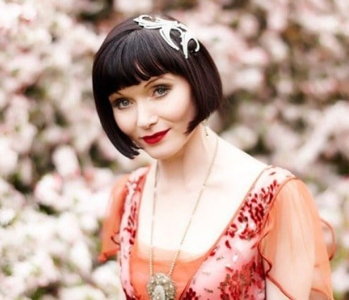 Woman with 1920s Jordan Baker inspired short bob hair with a fascinator, wearing a red cap sleeved dress