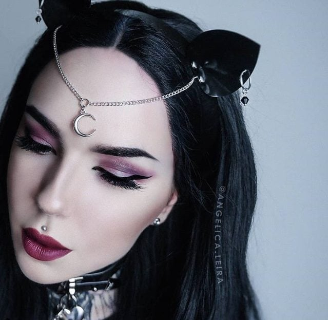 Goth hairstyles: Gothic woman with long dark brown hair, wearing cat ears with dangling moon hair chain with collar, posing in a studio