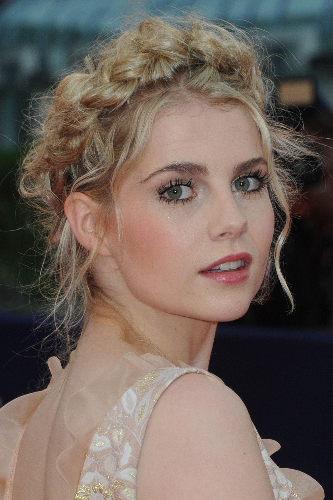 grecian hairstyles: close up shot of lucy boynton with romantic milkmaid braid hairstyle