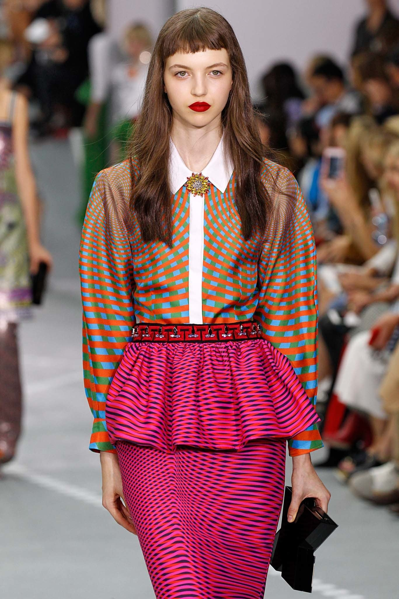 Short bangs: Model with long wavy brown hair and short micro fringe wearing a pattern shirt and skirt.