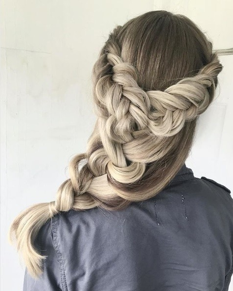 Medieval hairstyles: Back view of a woman with ash blonde long hair in a big oversized side braid
