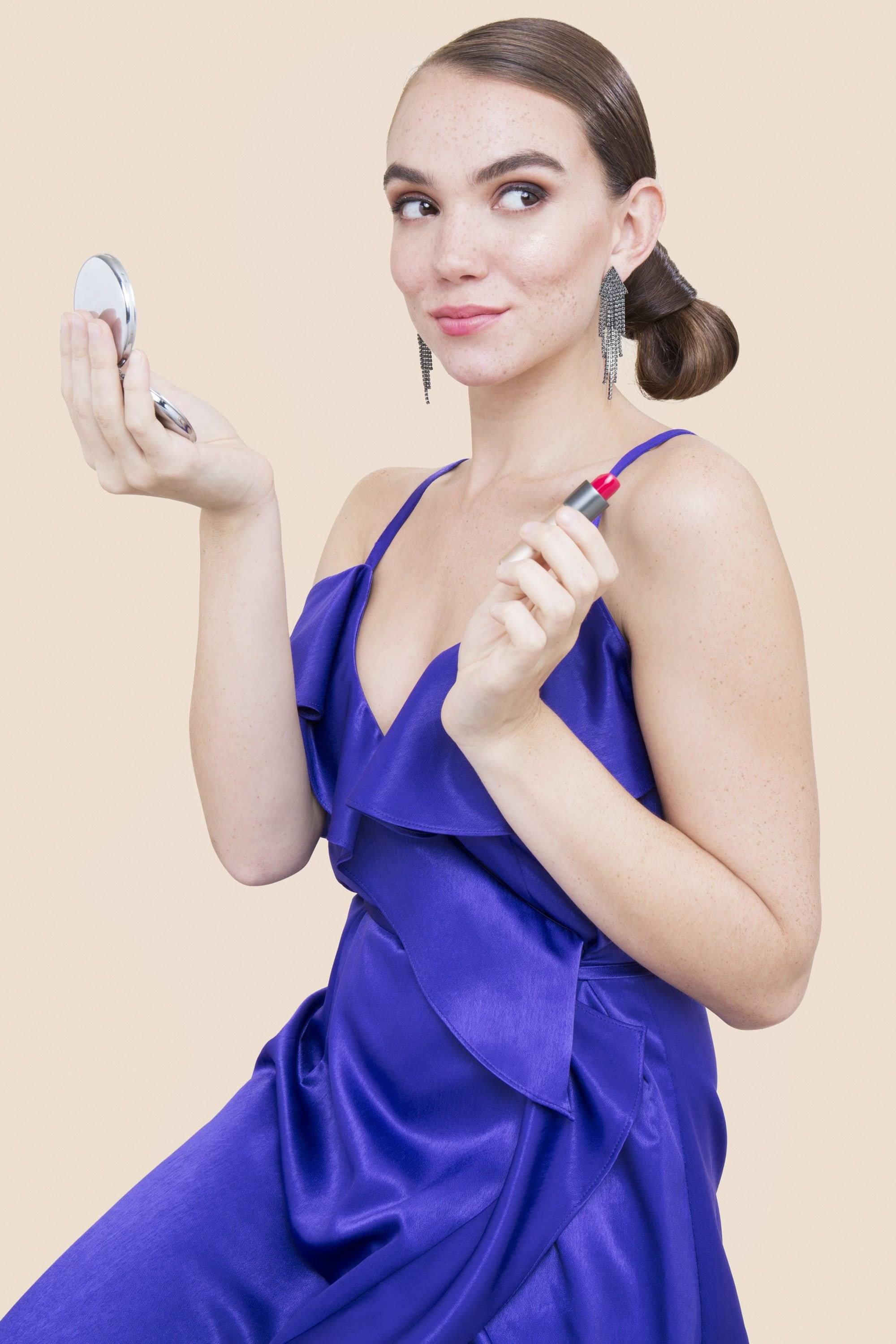shot of model in the studio with sleek low side bun, wearing blue dress and holding makeup