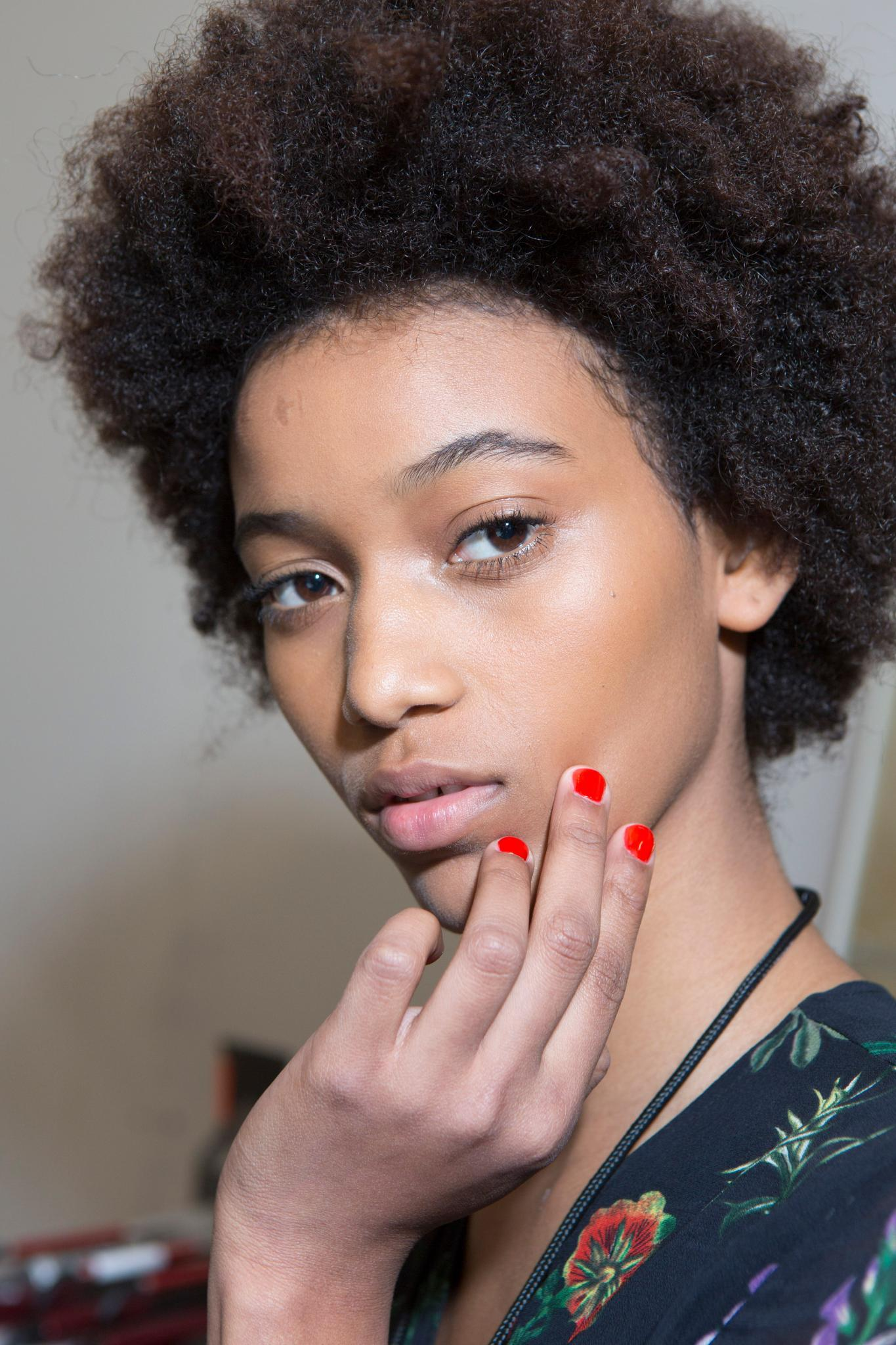 Detangling natural hair guide: Backstage shot of model with natural hair, with red nails and smiling