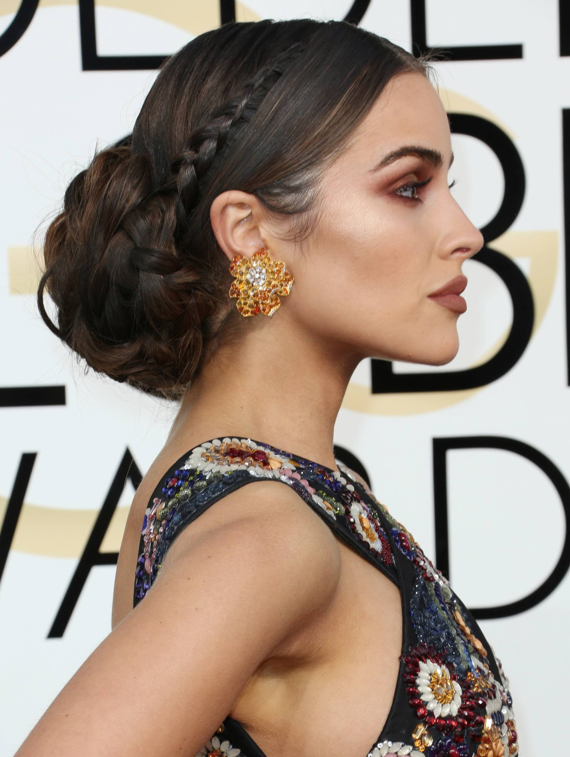 greek hairstyles: side shot of oliviia culpo with braided low bun hairstyle