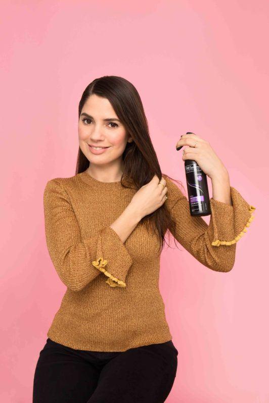 a woman spraying her long brunette hair
