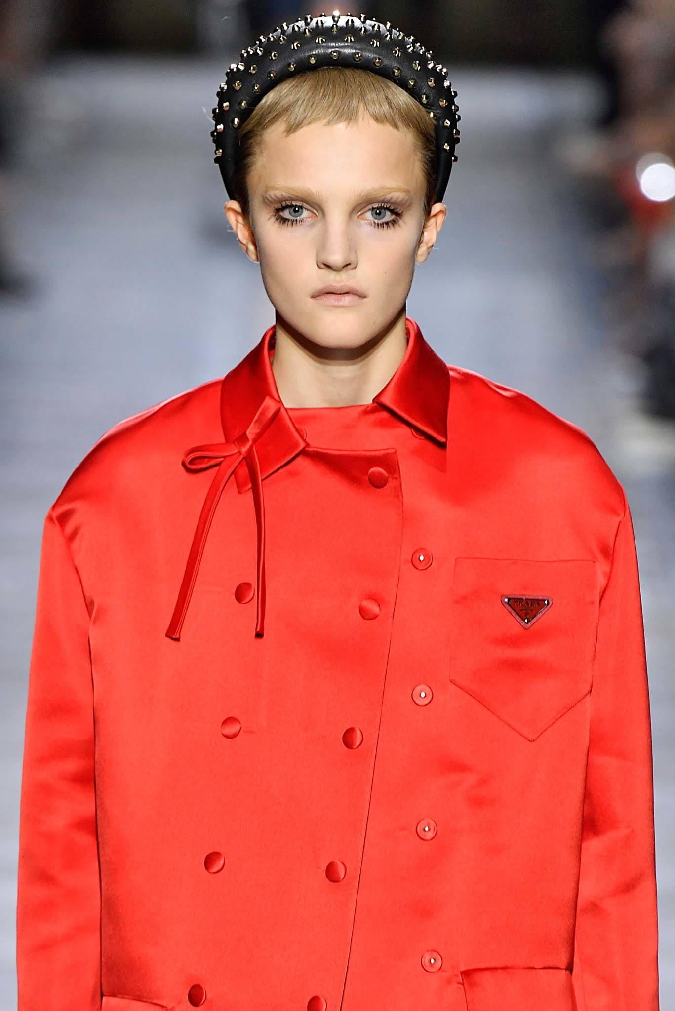 Short bangs: Model with blonde hair wearing a large headband with micro bangs at Prada.