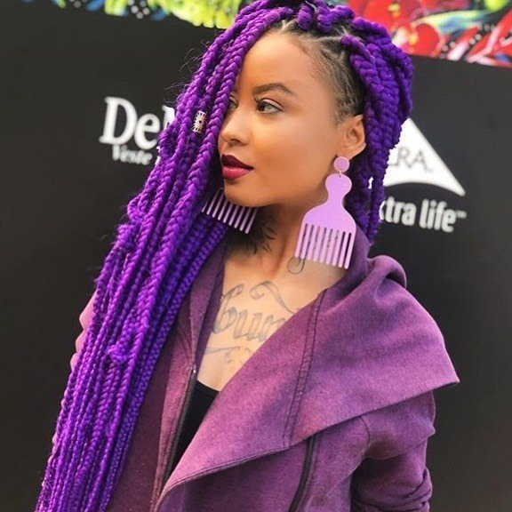 Woman with purple long box braids with temple shaved undercut