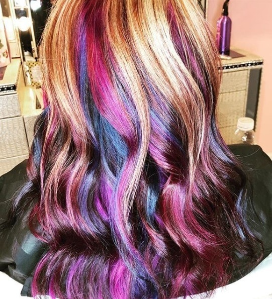 Unicorn hair: Back view of a woman with reddish brown curly hair with purple and pink highlights
