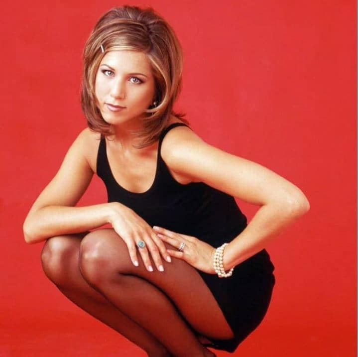 Rachel haircut: Jennifer Aniston with shoulder length brown highlighted hair with long layers wearing a black dress in front of a red backdrop
