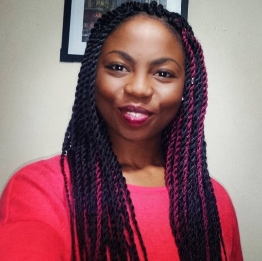 Woman wearing a red tshirt with long dark box braids with peekaboo red coloured sections