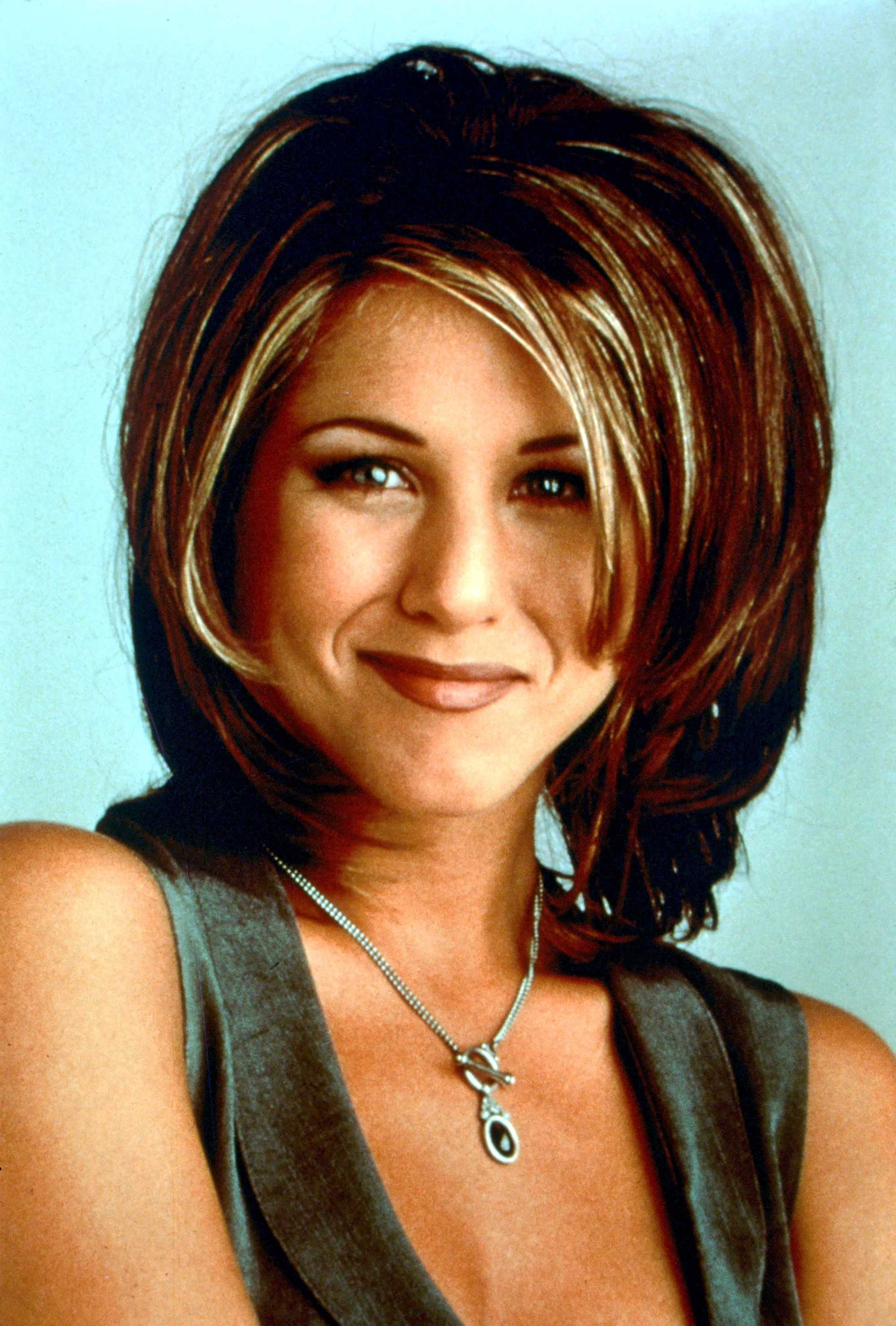 Rachel haircut: Jennifer Aniston with shoulder length volume bob with long layers and side fringe 90s hairstyle.