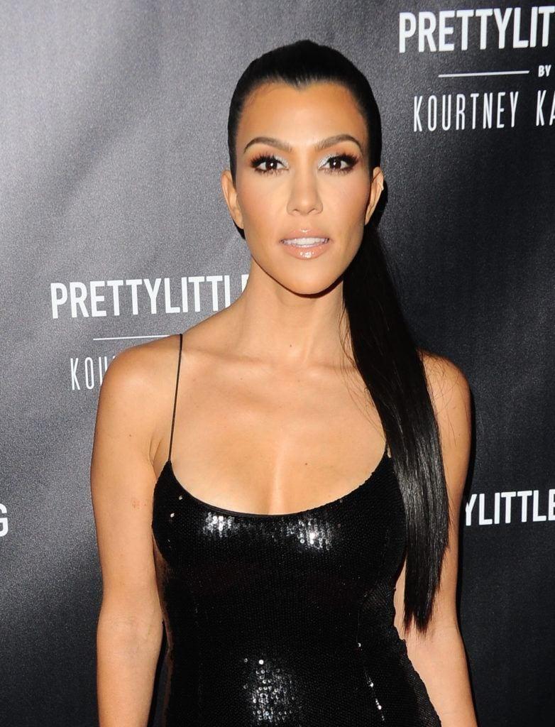 Kourtney Kardashian dark long hair in high ponytail over one shoulder