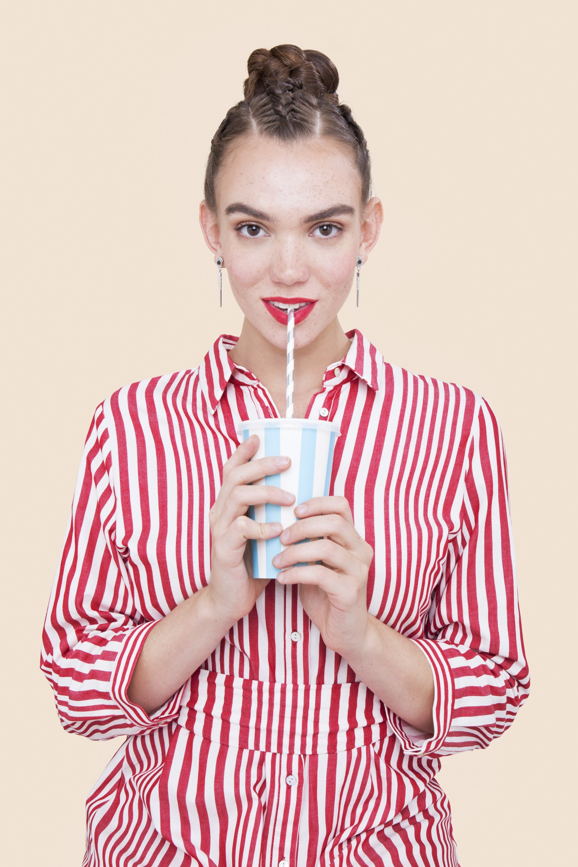 close up shot of model with red striped shirt and braided bun hairstyle