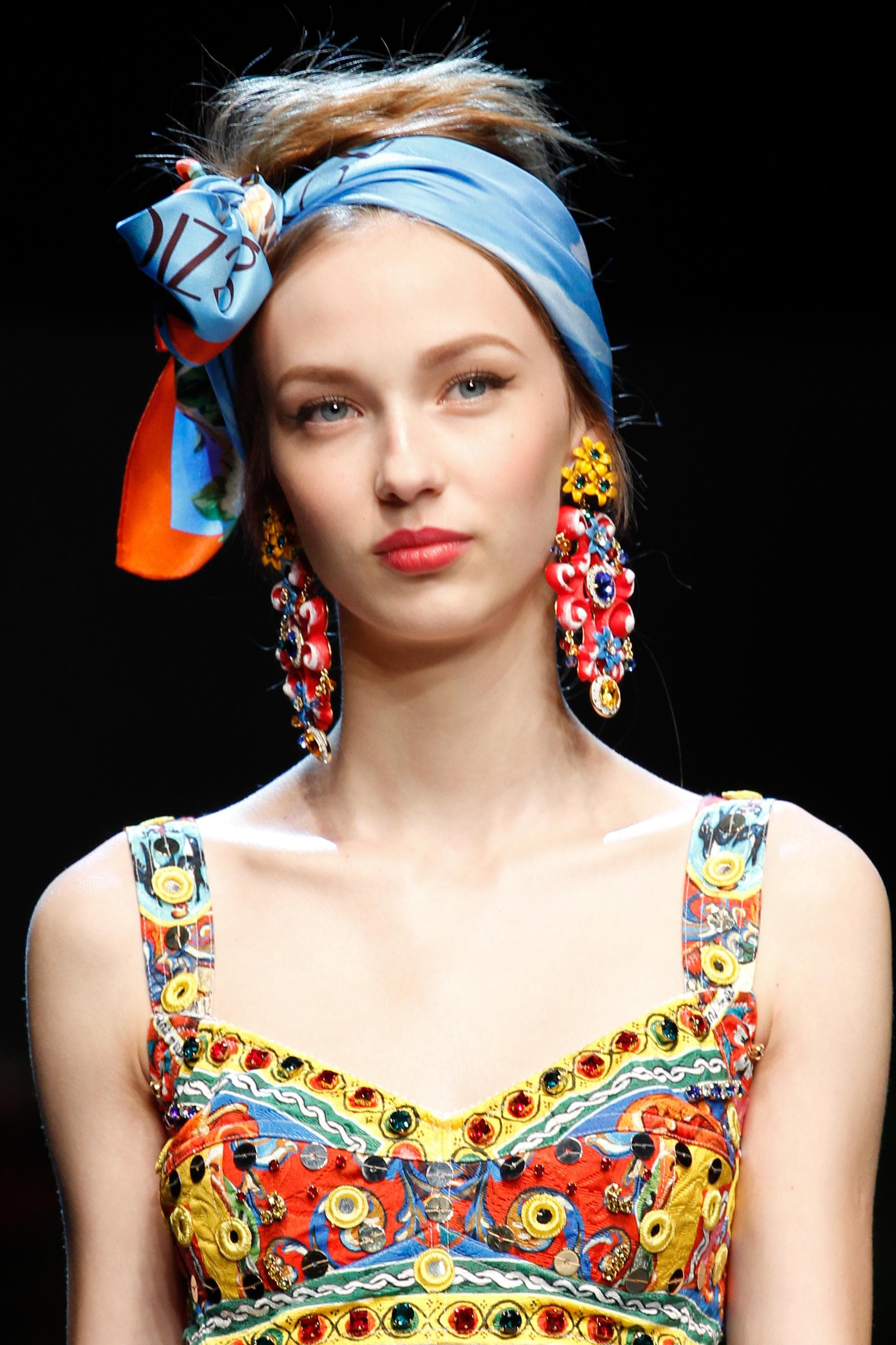 vintage updo hairstyles: close up shot of model with scarf hairstyle on the runway posing