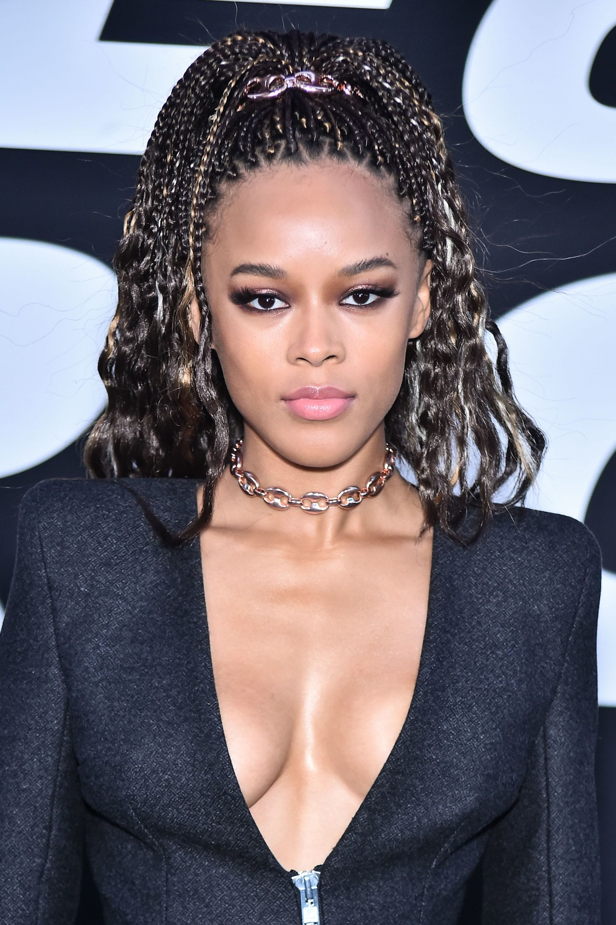Loose box braids: Close up shot of Serayah McNeill with medium brown box braids with curly ends, styled into a high ponytail.