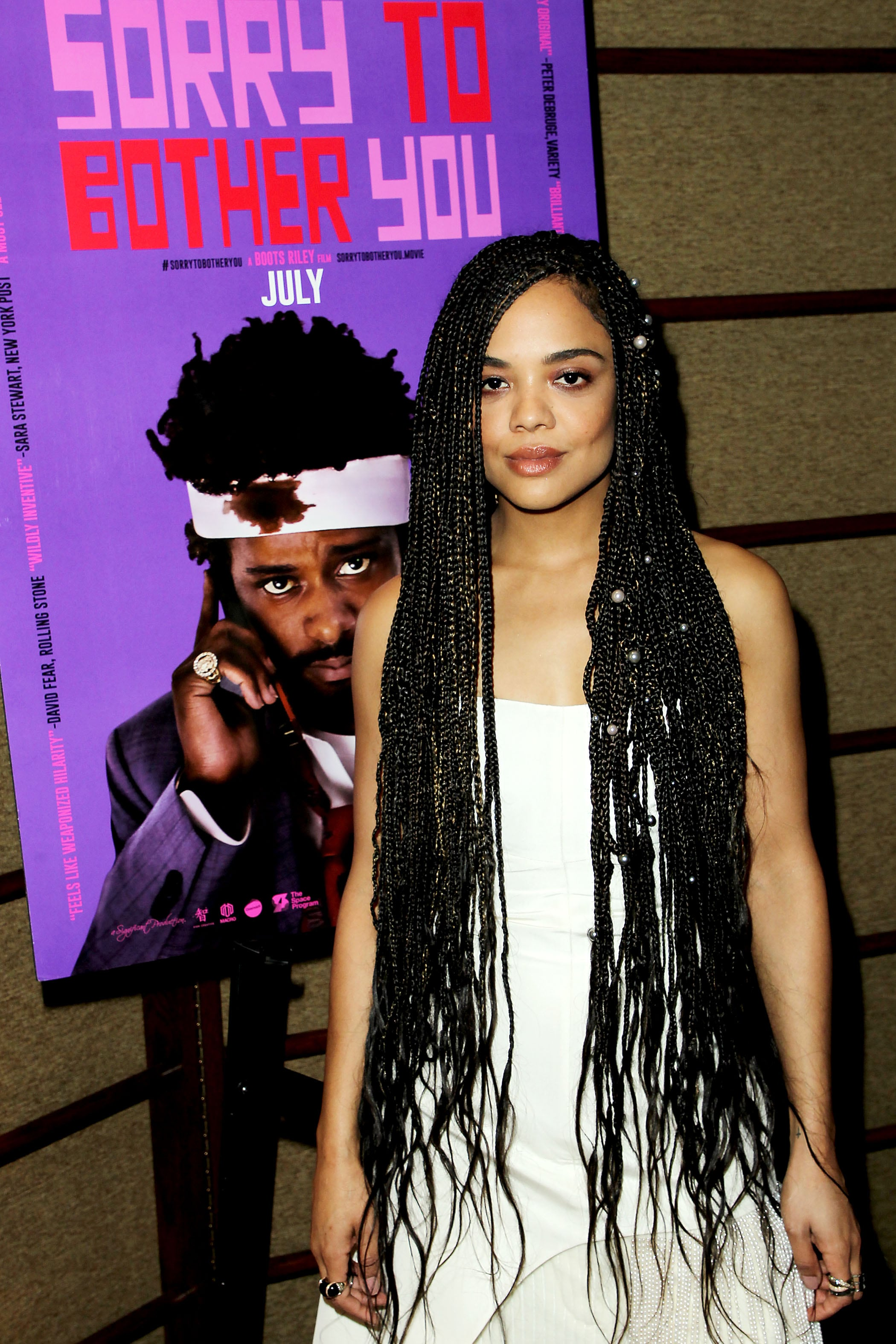 Loose box braids: Close up shot of Tessa Thompson with long, dark brown box braids with loose ends, decorated with pearls, wearing a white dress and posing at an event.