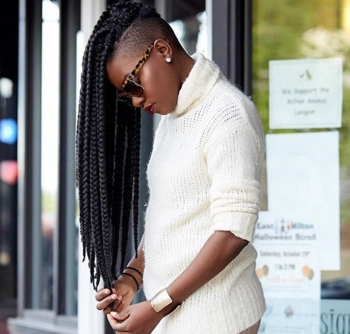 shot of woman with long box braids with shaved back and sides, posing on the street