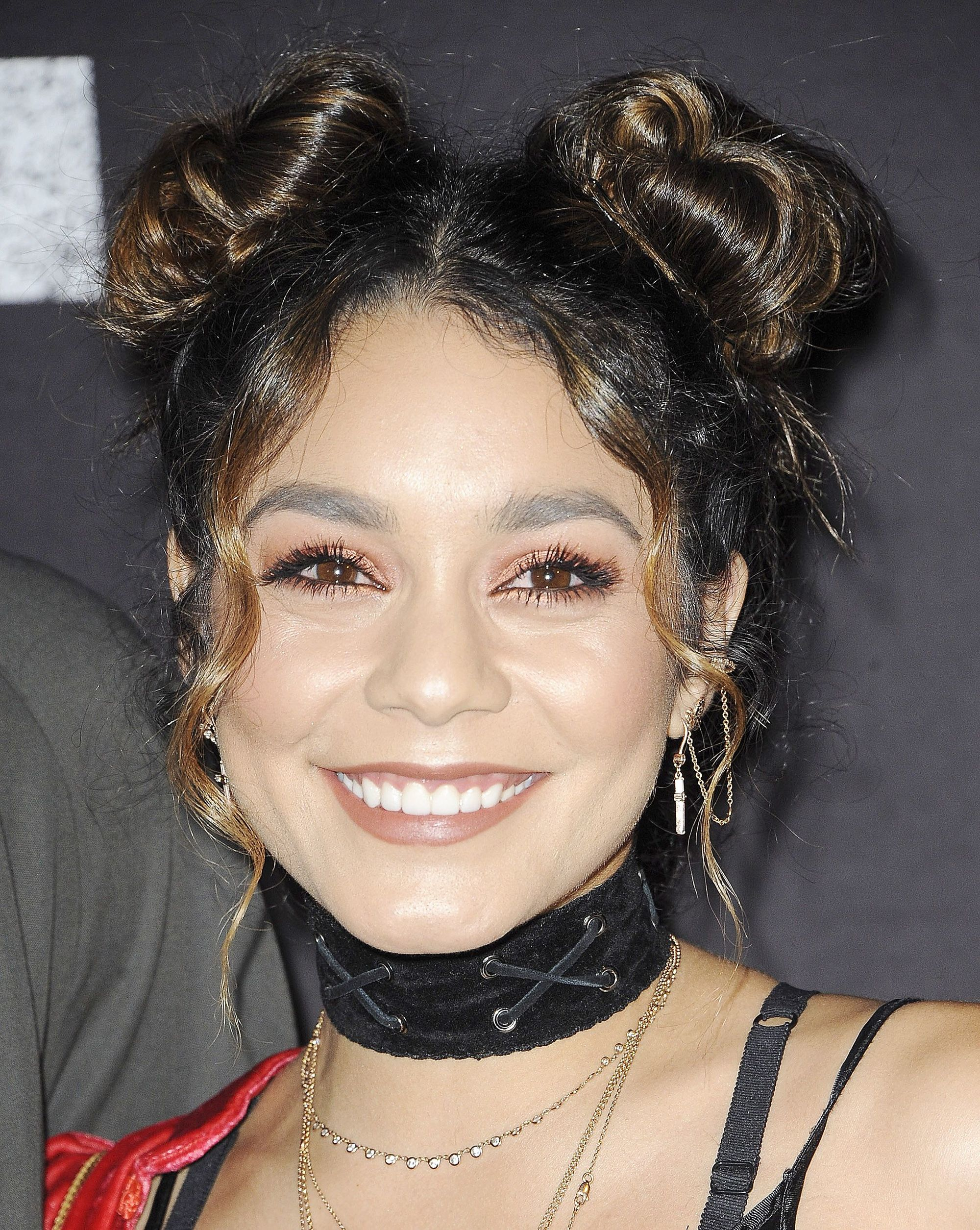 90s hairstyles: Vanessa Hudgens space buns hairstyle with loose tendrils along the hairline