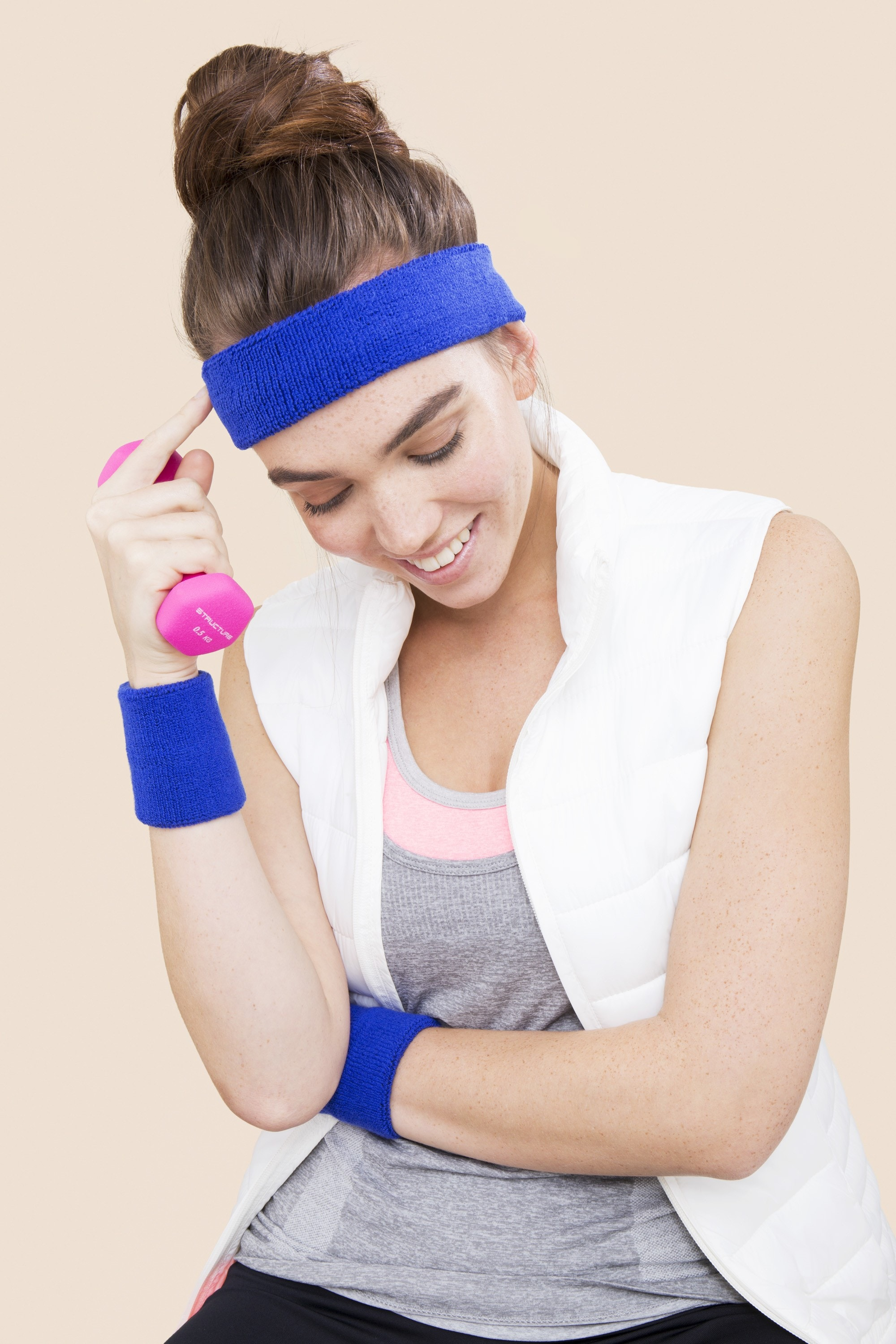 close up shot of model in the studio with topknot hairstyle, wearing gym clothing and holding weights