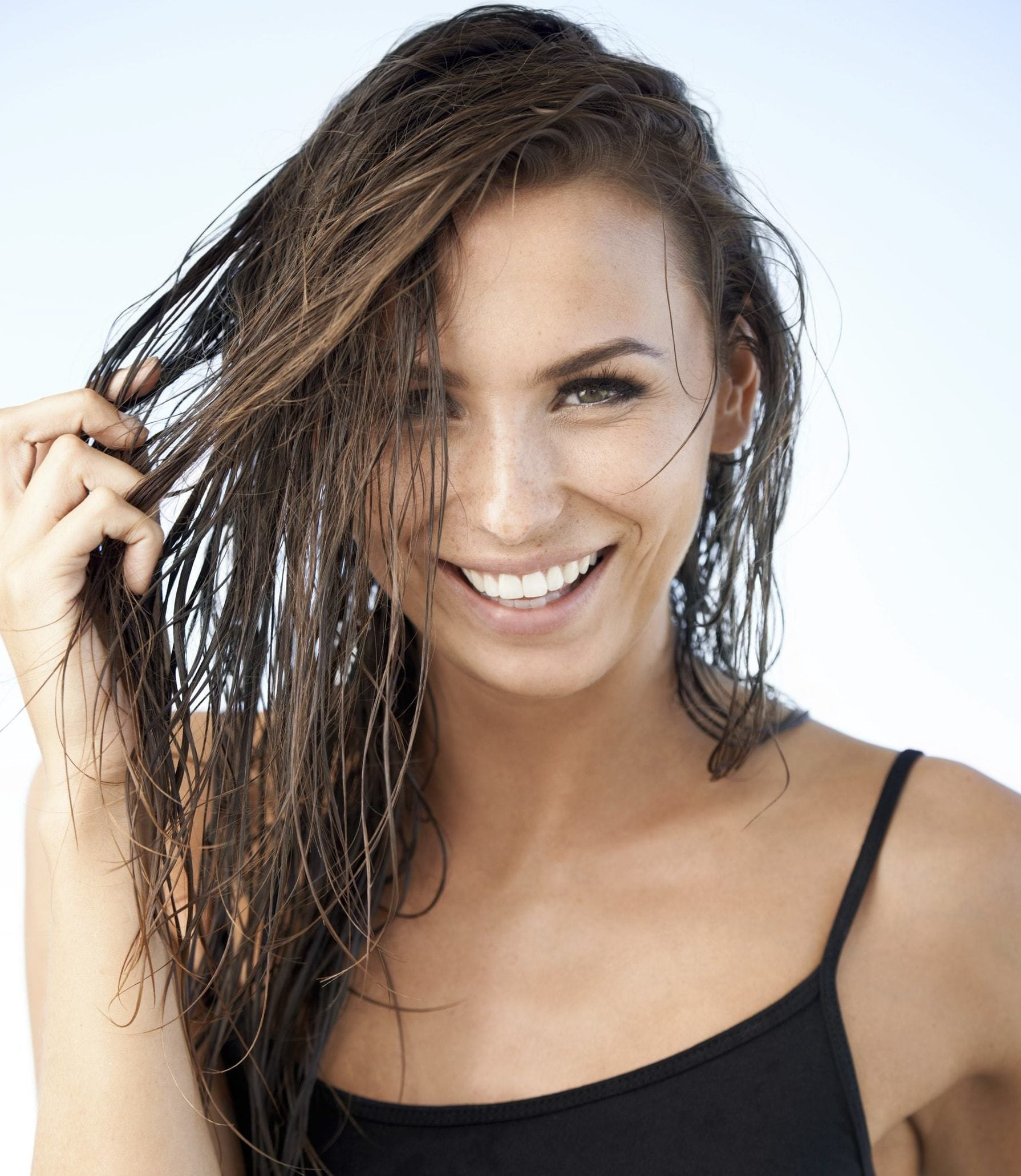 brunette model with damp hair running hands through the side