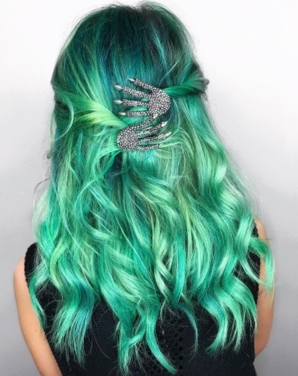 Witch hair: Back shot of a woman with green balayage curly hair in a half up half down twisted style adorned with hand shaped hair clips