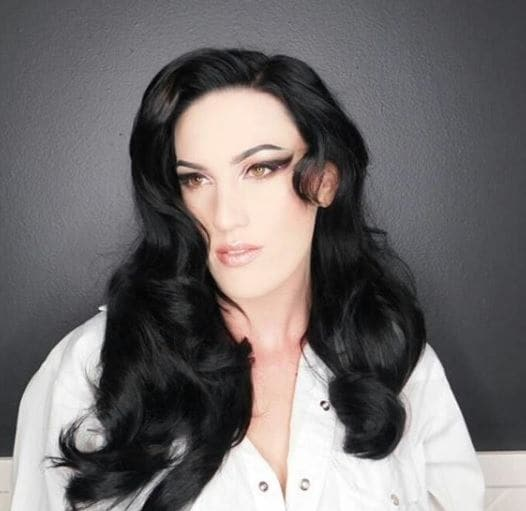 Witch hair: Close-up photo of a woman with long jet black curled hair, wearing a white shirt