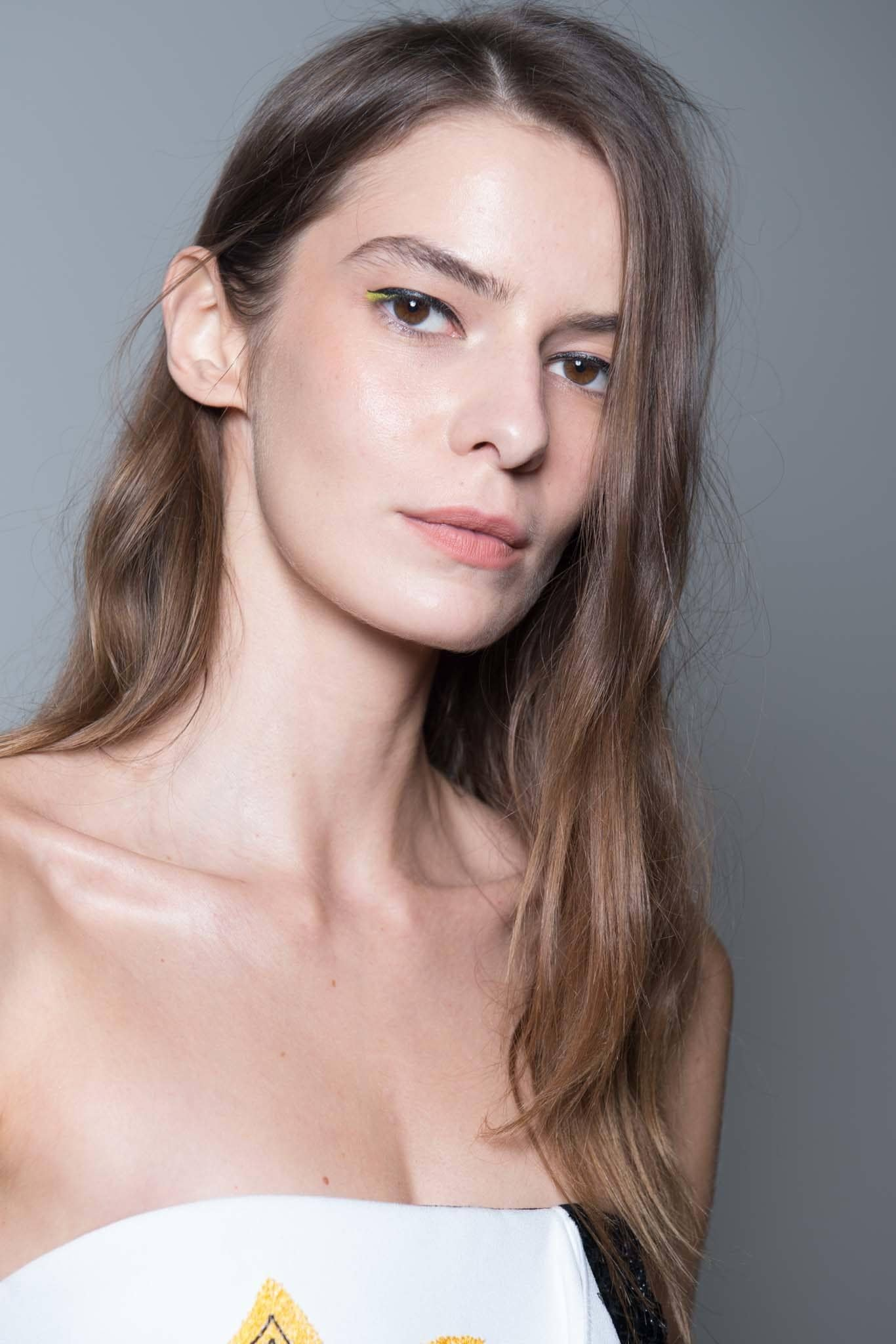 backstage shot of model with straight hair that has a few waves in it, posing