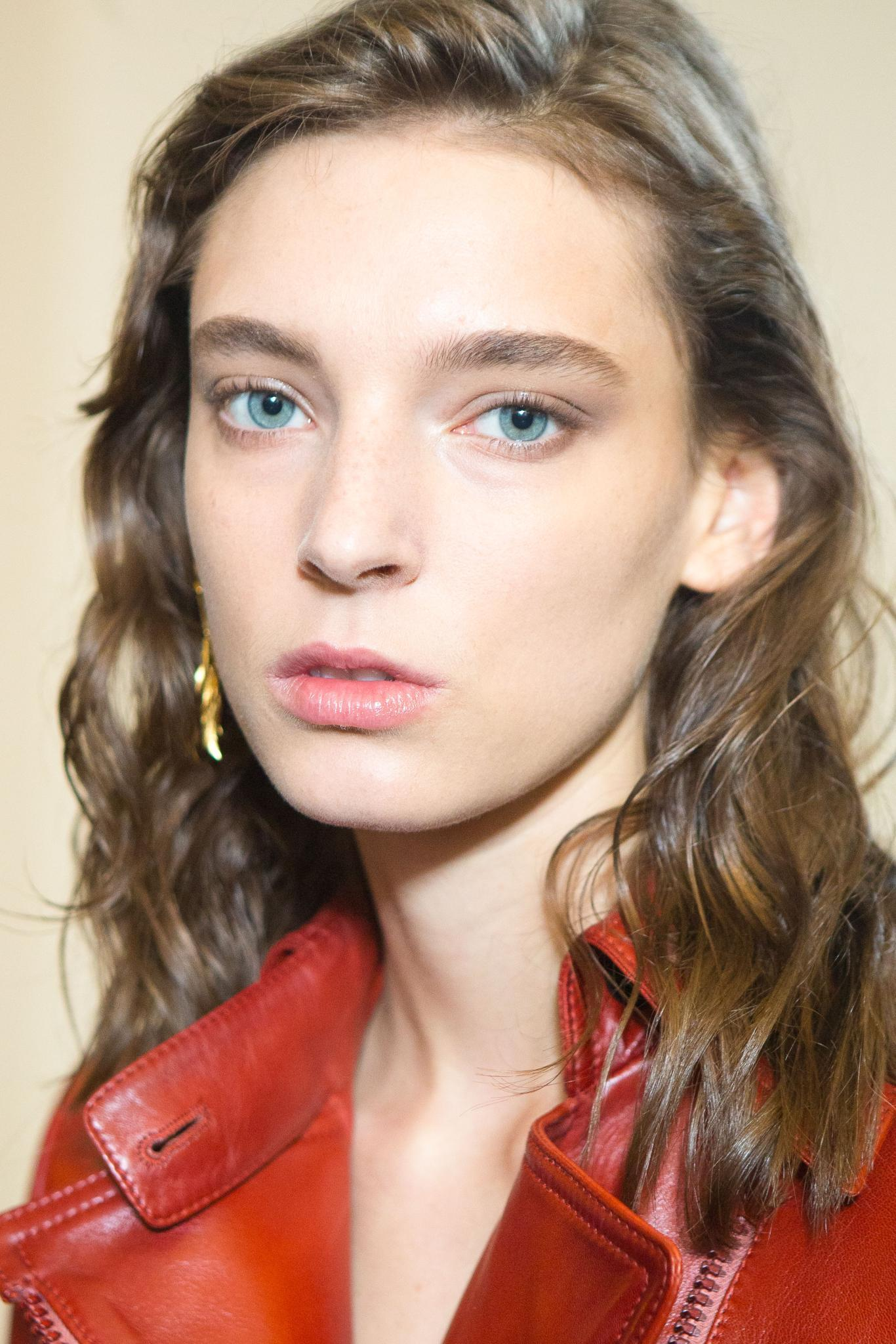 close up shot of model with 2B hair, wearing red shirt and gold earrings, posing