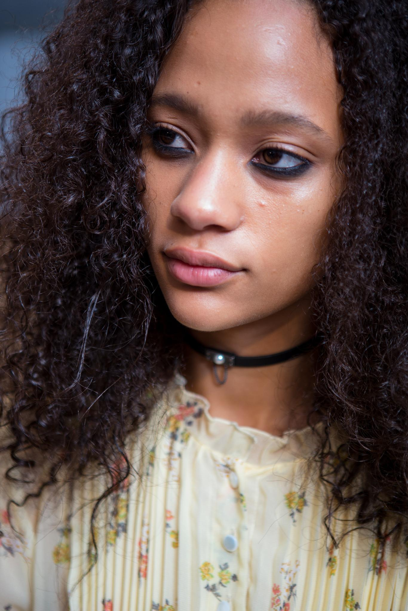 backstage shot of model with long curly hair with a choker, wearing a flora